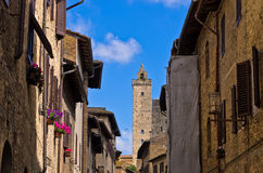 Medieval architecture of San Gimignano, towers and houses decorated with flowers, Tuscany Stock Photos