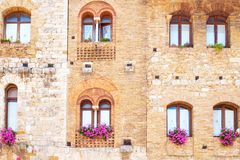 The medieval architectures of San Giminiano. San Giminiano, Italy, viiew of the facade of a medieval palace in Della Cisterna square Stock Photo