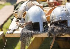 Medieval armor, helmets  lie on a wooden table outdoor. Royalty Free Stock Images