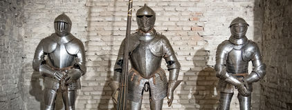 Medieval armor knight steel metal horizontal brick wall brown Stock Photos