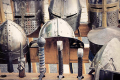 Medieval armors: helmets and swords Royalty Free Stock Images