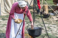 Medieval Arts Festival 2015 - Suceava Medieval Crown Fortress. Suceava, Romania - August 15th 2015 - Woman dressed as a peasant boiling eggs at the Medieval Arts Stock Photography