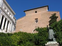 Medieval basilica of Saint Maria in Aracoeli in Rome in Italy with of forehead a statue. Blue clear sky. Sunny day. Spring time. Green plants and shrubs Royalty Free Stock Image
