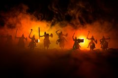 Medieval battle scene with cavalry and infantry. Silhouettes of figures as separate objects, fight between warriors on dark toned. Foggy background. Night scene royalty free stock images