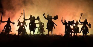 Medieval battle scene with cavalry and infantry. Silhouettes of figures as separate objects, fight between warriors on dark toned royalty free stock photo