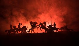 Medieval battle scene with cavalry and infantry. Silhouettes of figures as separate objects, fight between warriors on dark toned. Foggy background. Night scene royalty free stock photo