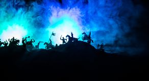 Medieval battle scene with cavalry and infantry. Silhouettes of figures as separate objects, fight between warriors on dark toned. Foggy background with stock image
