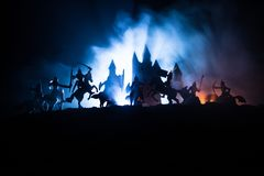 Medieval battle scene with cavalry and infantry. Silhouettes of figures as separate objects, fight between warriors on dark toned. Foggy background with royalty free stock photo