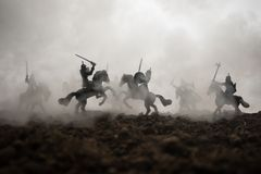 Medieval battle scene with cavalry and infantry. Silhouettes of figures as separate objects, fight between warriors on sunset