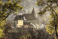 Medieval Brasov during autumn. The gothic Black Church. Medieval city of Brasov, Transylvania, Romania. A view through the trees making a frame for the gothic Stock Photography