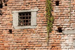 Medieval brick wall - Window with wrought iron bars. Detail of a medieval brick wall with a window with wrought iron bars and a creeper plant, Italy, Europe royalty free stock photography