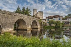 Medieval bridge in France. Medieval bridge with the castle of Bourdeilles in the background Royalty Free Stock Images