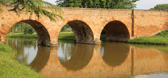 Medieval bridge made of red brick with arches over the river. Medieval bridge made of red brick with three arches over the river in Europe Royalty Free Stock Photos