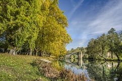 Medieval bridge over Arnoia river in Allariz, Ourense, Spain, in. Reflection of river and medieval bridge in Allariz in autumn , Orense, Galicia, Spain Royalty Free Stock Image