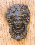 Medieval bronze knocker on the wooden door Stock Photo