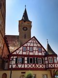 Medieval building in front of church tower Royalty Free Stock Photography