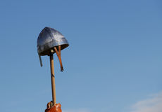 Medieval Casque. Old-fashion warrior helmet held high at top of wooden pole against a blue sky. The head-wear is viking or gladiator like and used in enacting Royalty Free Stock Images