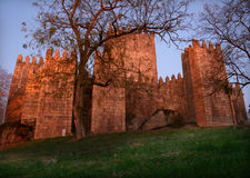 Medieval castle. Medieval buildings on a green field by night Stock Images