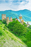 The medieval castle at Aragvi River. The old stone towers and Assumption Church's dome of Ananuri Castle among the greenery on the steep slope at Aragvi River Stock Photos