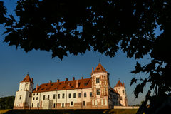 Medieval castle in the Belorussian town of Mir framed by the silhouettes of leaves of trees Royalty Free Stock Images
