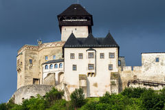 The medieval castle of the city of Trencin in Slovakia. An ancient medieval castle on the hill light among green trees in the city of Trencin in Slovakia Stock Photo