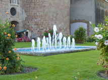 Medieval Castle Fountain. XIII century castle in Morges, Switzerland hosts a simple fountain in its courtyards, surrounded by well taken take of vegetation Royalty Free Stock Photo