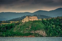 Medieval Castle on the hill surrounded by the lake in the mountains. stock photo