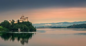Medieval Castle on the hill surrounded by the lake in the mountains. stock photography