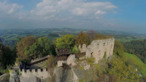 Medieval castle in the middle of beautiful landscape. Helicopter camera zooming-out footage of business meeting on the castle ruins with the beautiful view on stock video