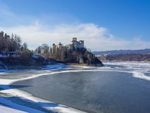 Medieval Castle in Niedzica, Poland, in winter. Frozen artificial Czorsztyn lake on Dunajec river and the far view of Czorsztyn castle in sunset light stock photography
