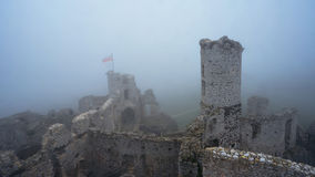 Medieval castle ruin in heavy fog view from high point Royalty Free Stock Image