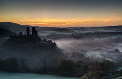 Medieval castle ruins with foggy landscape at sunrise Royalty Free Stock Photography