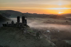 Medieval castle ruins with foggy landscape at sunrise Royalty Free Stock Image