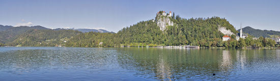 Medieval castle, St. Martins Parish Church and Bled Lake panoram royalty free stock photos