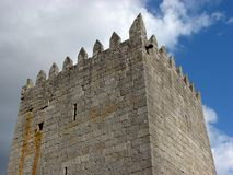 Medieval castle stone tower. Medieval castle stone tower with battlements against the sky on a cloudy day Stock Photos