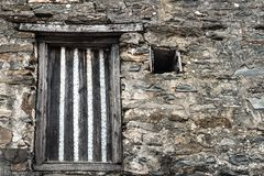 Medieval castle stone wall texture with boarded up window. Old medieval castle stone wall texture under natural light with boarded up window background royalty free stock images