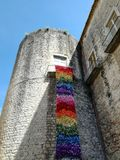 Medieval castle tower with balcony with colorful flower mantle on holiday Royalty Free Stock Photography