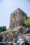Medieval castle tower built on rock with stariways leading to to. Medieval castle tower built on rock with stairways leading to tower shot from lower perspective Royalty Free Stock Image