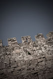 Medieval castle wall. Top of a medieval castle wall against sky. Toned, vignette added Royalty Free Stock Photo