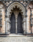 Medieval Cathedral doors surrounded by religious statues. Royalty Free Stock Photos