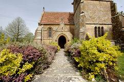 Medieval Church. Medieval English Village Church with colourful shrubs bordering the path Royalty Free Stock Photo