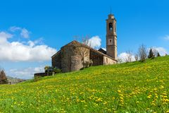 Medieval church on spring field in Italy. Stock Photos