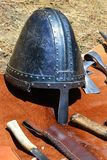 Medieval conical helmet also called norman casque with nosepiece displayed with knives and light battleaxe head displayed on orang Royalty Free Stock Photo