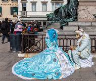 Medieval Costumes Scene. Venice,Italy,February 26th 2011: A couple disguised in specific sophisticated Venetian costumes poses for tourists while smoking on Stock Photo