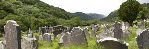 Medieval country graveyard. Ancient country graveyard at the historic, Medieval Glendalough Monastery, County Wicklow, Ireland. Wide angle panorama stock photos