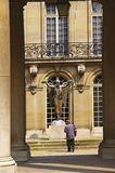 Medieval courtyard in Paris. Architectural details with sculpture and tourist in background royalty free stock photo