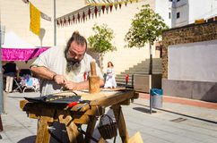 Medieval craftsman making arrows in market Royalty Free Stock Photography