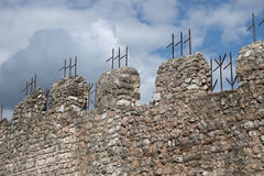Medieval crenellated walls. Ancient medieval walls with battlements and iron spades Royalty Free Stock Image