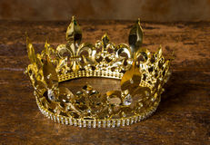 Medieval crown. Medieval style golden crown on antique wooden background Stock Image