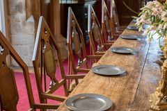 Medieval dining table and chairs. Mediaeval fraternal banqueting. Medieval dining table and chairs. Mediaeval period banquet table set with metal plates. Fine royalty free stock photo